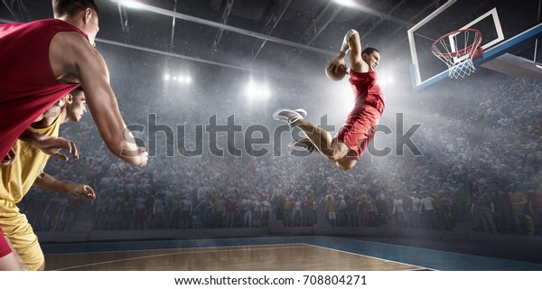 Basketball players on big professional arena during the game. Basketball player makes slam dunk. Players are wearing unbrand clothes.