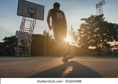Basketball players playing basketball outdoor.