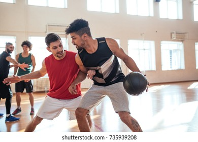 Basketball players practicing on the court.