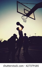 Basketball players silhouettes. (Retro toned image with selective focus)
