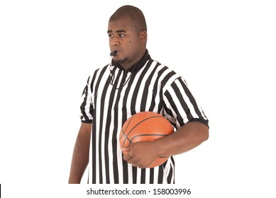 Basketball referee with ball blowing the whistle