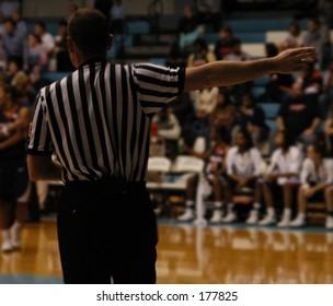 basketball referee calling the ball for white