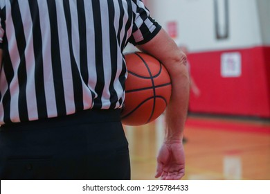 A basketball referee holds a ball during a timeout