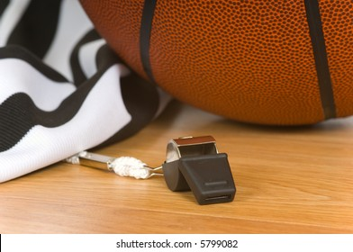 Basketball referee items including a whistle, a jersey and a basketball on a gym floor