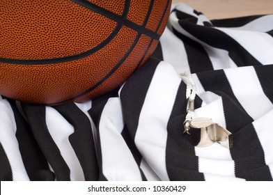 A basketball referees items including a ball, a striped jersey and a whistle