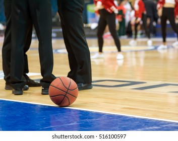 A basketball rests on the court at halftime. Near the ball are the referee of the match