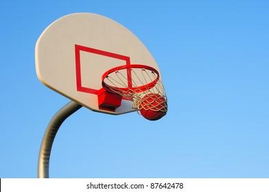 A basketball shot swishes through an outdoor hoop