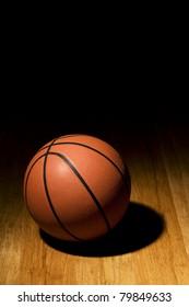 Basketball sitting on basketball court in the spotlight.