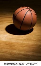 Basketball sitting on hardwood floor in spotlight.
