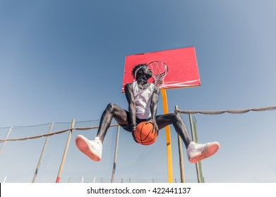 Basketball street player making a rear slam dunk - Sporty black man playing basketball outdoor