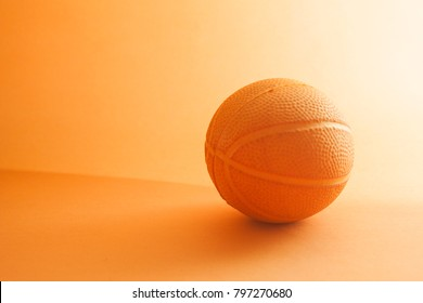 a basketball toy on a orange background