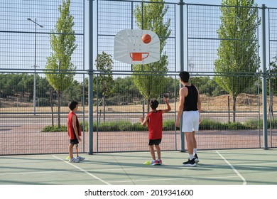 Basketball trainer showing how to shoot basketball to a two children, one of them has a leg prosthesis. Coach training two kids.