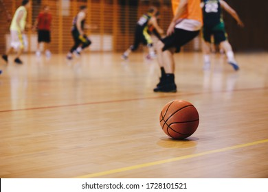 Basketball Training Session. Basketball Game Background. Basketball on Wooden Court Floor Close Up with Blurred Players Playing Basketball Practice Training Game in the Background