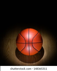 Basketball under spotlight on Gym Floor