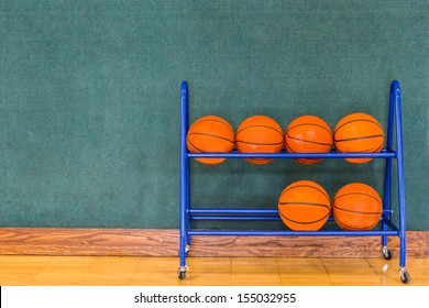 Basketballs stored in a blue metal storage rack along a blue green wall on a gym floor. Copy space.