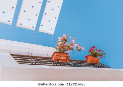 baskets, boxes of flowers hanging on the railings of a balcony on a white building typical of the algarve and southern spain. strips of polka dot sunshade are attached to the roof.