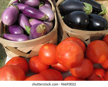 Baskets of bright red tomatoes and purple eggplant brighten a farmers market.