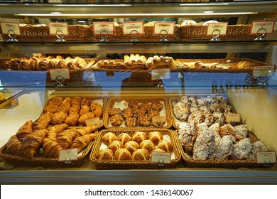 Baskets of butter croissant,Almond chocolate croissant,Hot cross bun,Ham and cheese Tiger claw,Bacon and ham sandwiches,Kouign Amann and Maple pull apart displayed in glass showcase box