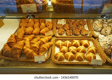 Baskets of butter croissant,Almond chocolate croissant,Hot cross bun and Maple pull apart displayed in glass showcase box