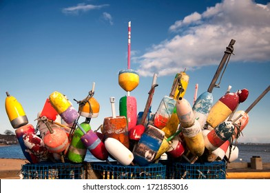 Baskets of colorful fishing and lobster buoys on a wharf in Provincetown, Massachusetts on a sunny cape cod day.