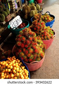 Baskets containing exotic fruits such as rambuton, lychee and durian in Thai outdoor market.