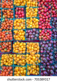 Baskets of fresh picked colorful cherry tomatoes on display at local farmer's market. Can be used as a healthy food background.