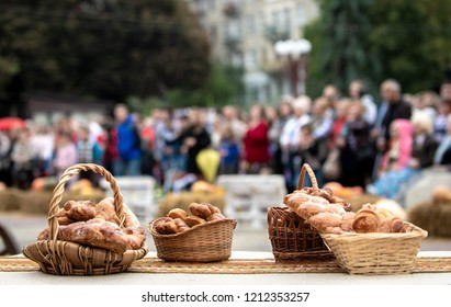 baskets full of various bread loaves at a harvest festival in the city