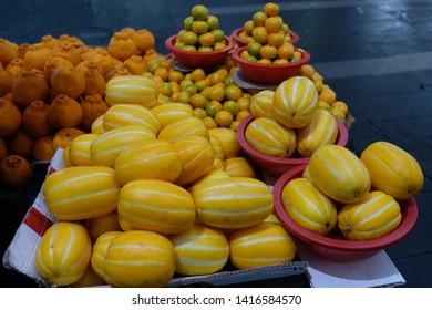 Baskets of Oriental melons (Cucumis melo) and mandarin oranges (Dekopon) sold by fruit vendor