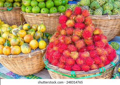 Baskets at a street market full of tropical fruit: rambutan, passion fruit, sapote, chirimoya, lime
