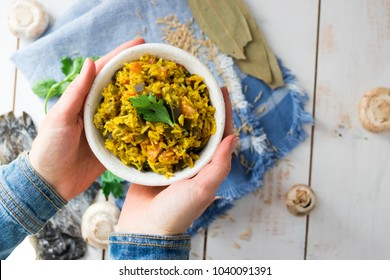 Basmati brown Indian rice with quinoa, raw tomatoes, celery, garam masala spices, champignons mushrooms and herbs in woman's hands. Organic ingredients. Raw, vegan, vegetarian healthy food concept.