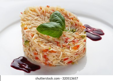 basmati rice on a white plate with basil leaves