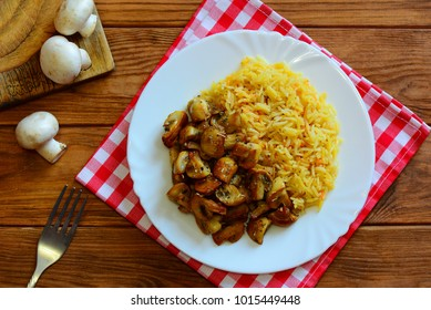 Basmati rice with roasted mushrooms on a white plate on a wooden background. Vegan diet menu. Quick vegetarian main course recipe. Basmati rice cooking. Closeup. Top view
