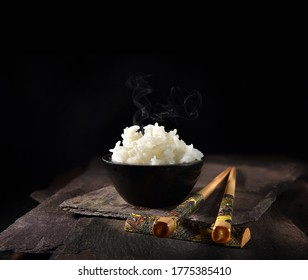 Basmati rice steaming in a small black ceramic crucible with genuine antique hand-decorated bamboo chop sticks on black slate. Shot against a black background with accommodation for copy space.