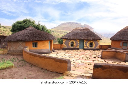 Basotho tribe village. Clay huts rondavels with the straw roof. Cozy courtyard with the cruciform cooking place. Traditional tribal lifestyle. Ethnic houses surrounded by the wild untouched nature.