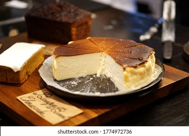 Basque burnt cheesecake - A tray of homemade cheesecake on table and blurred background, Delicious spanish dessert recipe.