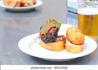 Basque tapas or pintxos with beer in San Sebastian, selective focus
