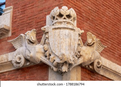 Bas-relief of old coat of arms shield on the entrance with fcatalan flag, dragons and crown