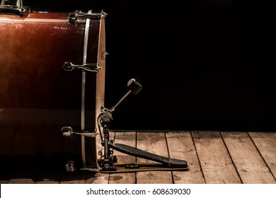 bass drum with pedal on wooden floor with a black background
