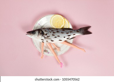 A bass fish with arms and legs of a doll inside on a flower plate. Cannibalism and anthropomorphism on a pink feminine background. quirky minimal color still life photography.