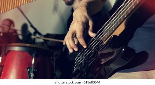 Bass guitar in hands of musician. Musical background