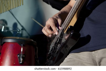 Bass guitar in hands of musician. Musical background