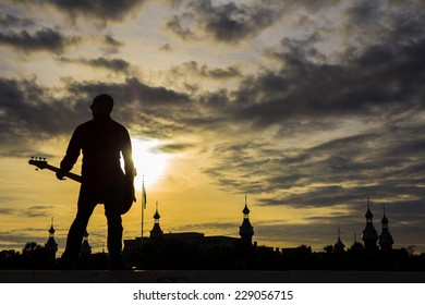 Bass guitar player against sunset background