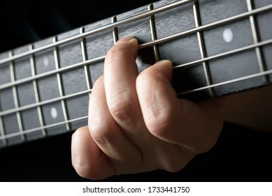 Bass guitar player hand close-up, concept of playing on bass electric guitar, live music and skill. Guitarist fingers on bass fretboard or fingerboard and frets. Lesson and practice theme.