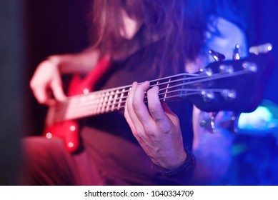 The bass guitar player is on stage in the bright red and blue lights of the spotlights. Selective focus.