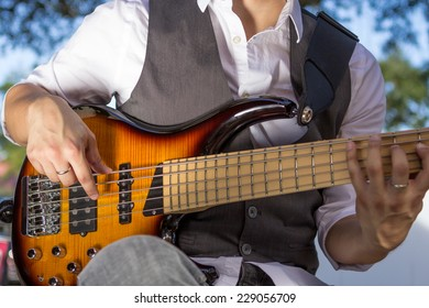 Bass guitar player outdoors in dress clothes