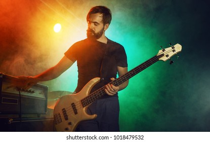 The bass guitarist connects the bass guitar to the amplifier on the stage. Stage light. Smoke.