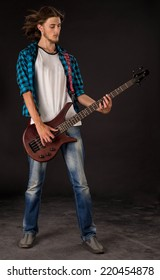 Bass guitarist. Located on the black background.