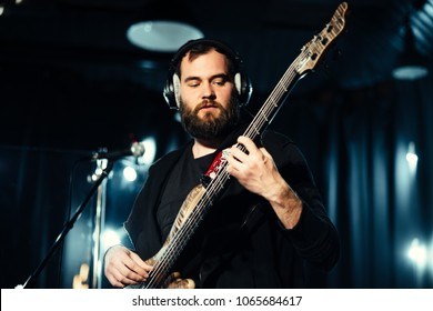 Bass guitarist playing with band in the dark music studio
