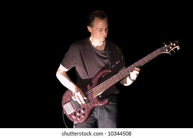 Bass Guitarist playing while isolated on black during live concert