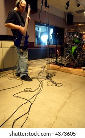 A bass player recording his tracks in a recording studio with natural outside light streaming into the control room.  Slow shutter speed with ambient light - player has motion blur from slow shutter.